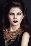 Portrait de plan rapproché avec l'oeil bleu profond, le maquillage créatif et les accessoires d'or Photographie stock libre de droits