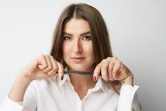 Portrait de plan rapproché de belle jeune femme dans des mains d'un stylo de participation de chemise de blanc et de regarder l'a photo libre de droits