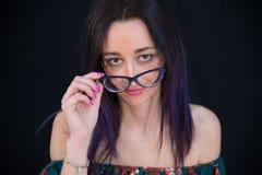 Portrait de plan rapproché de belle jeune fille avec des verres, fond noir photos stock