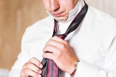 Portrait de plan rapproché d'homme d'affaires bel dans le costume mettant sur la cravate à l'intérieur photos stock