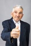 Portrait de plan rapproché d'homme plus âgé montrant le pouce  Photo libre de droits