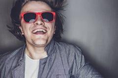 Portrait de plan rapproché d'un jeune homme occasionnel avec des lunettes de soleil Image libre de droits