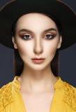 Portrait de plan rapproché d'une belle fille dans le chapeau sur un backgr gris photographie stock libre de droits