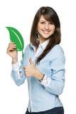 Femme de sourire d'affaires tenant la feuille d'eco Photographie stock libre de droits