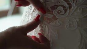 Portrait de plan rapproché d'une domestique ou d'une mère aidant la jeune mariée à porter sa robe banque de vidéos