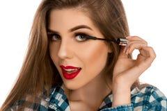 Portrait de plan rapproché d'une fille avec une brosse de maquillage pour la mèche à disposition Image stock