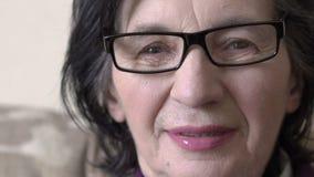 Portrait de plan rapproché, dame âgée heureuse avec des lunettes souriant et regardant l'appareil-photo clips vidéos