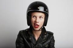 Portrait de plan rapproché de femme de cycliste au-dessus du fond blanc, du casque folâtre noir élégant de port et de la veste en Photographie stock