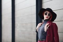 Portrait de plan rapproché de jeune belle femme à la mode avec des lunettes de soleil Madame posant sur le fond en bois gris modè Photos libres de droits