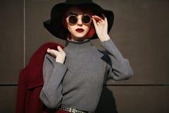 Portrait de plan rapproché de jeune belle femme à la mode avec des lunettes de soleil Madame posant sur le fond gris-foncé modèle Photos libres de droits