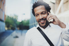 Portrait de plan rapproché de l'homme africain américain de sourire à l'aide du smartphone pour appeler des amis à la rue ensolei Images libres de droits