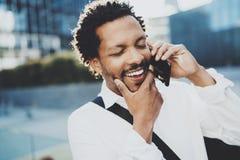 Portrait de plan rapproché de l'homme africain américain heureux à l'aide du smartphone pour appeler des amis à la rue ensoleillé Photos libres de droits