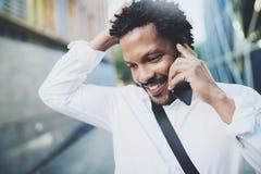 Portrait de plan rapproché de l'homme africain américain heureux à l'aide du smartphone pour appeler des amis à la rue ensoleillé Images libres de droits