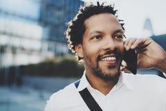 Portrait de plan rapproché de l'homme africain américain heureux à l'aide du smartphone pour appeler ses amis à la ville ensoleil Photos stock
