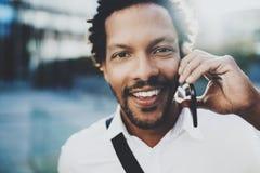 Portrait de plan rapproché de l'homme africain américain heureux à l'aide du téléphone portable pour appeler ses amis à la ville  Photos stock