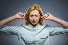 Portrait de plan rapproché de la femme inquiétée couvrant ses oreilles, observant N'entendez rien Photographie stock libre de droits