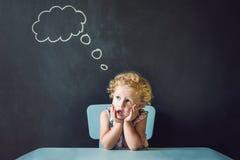 Portrait de plan rapproché de la petite fille mignonne pensant profondément à quelque chose l'espace de copie Images libres de droits