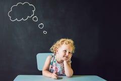 Portrait de plan rapproché de la petite fille mignonne pensant profondément au somet Images libres de droits