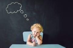 Portrait de plan rapproché de la petite fille mignonne pensant profondément au somet Photo libre de droits