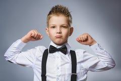 Portrait de plan rapproché de petit enfant drôle représentation de ses muscles de biceps de main L'enfant sérieux fort montrant s photos libres de droits