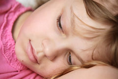 Portrait de plan rapproché de petite fille blonde menteuse Photos libres de droits