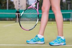 Portrait de plan rapproché des jambes femelles avec la raquette de tennis Photo libre de droits
