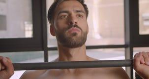 Portrait de plan rapproché des poids de levage d'homme caucasien musculaire sans chemise avec l'effort étant déterminé dans le gy banque de vidéos