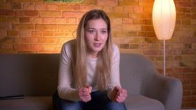 Portrait de plan rapproché des sportrs de observation femelles TV et célébration de jeune brune caucasienne attrayante avec l'emp clips vidéos