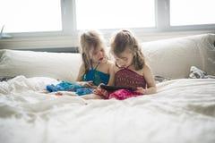 Portrait de plan rapproché de deux filles se trouvant sur le lit et à l'aide du comprimé Image stock