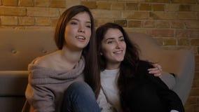 Portrait de plan rapproché de deux jeunes jolies femmes étreignant et regardant la TV avec l'excitation dans un appartement confo photographie stock libre de droits