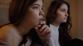 Portrait de plan rapproché de deux jeunes jolies femmes regardant la TV avec l'excitation dans un appartement confortable à l'int photo stock
