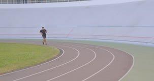 Portrait de plan rapproché du coureur masculin sportif caucasien adulte pulsant sur le stade dans la ville urbaine dehors banque de vidéos