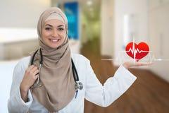 Portrait de plan rapproché du docteur féminin musulman sûr amical et souriant tenant le signe d'électrocardiogramme Photographie stock