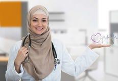 Portrait de plan rapproché du docteur féminin musulman sûr amical et souriant tenant le signe d'électrocardiogramme Images libres de droits