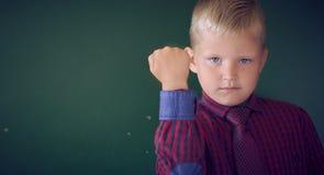 Portrait de plan rapproché du garçon caucasien fâché montrant le poing, justice exigeante, ses droites Fond vert de mur d'isoleme image stock