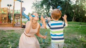Portrait de plan rapproché du garçon gai d'enfant en bas âge attrapant les bulles de savon colorées que sa mère souffle en parc image libre de droits