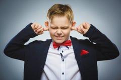 Portrait de plan rapproché du garçon inquiété couvrant ses oreilles, observant N'entendez rien Images libres de droits