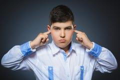 Portrait de plan rapproché du garçon inquiété couvrant ses oreilles, observant N'entendez rien Images stock