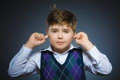 Portrait de plan rapproché du garçon inquiété couvrant ses oreilles, observant N'entendez rien Image libre de droits