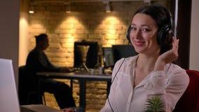 Portrait de plan rapproché du jeune employé de bureau féminin attirant dans des écouteurs écoutant la musique devant l'ordinateur clips vidéos