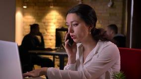 Portrait de plan rapproché du jeune employé de bureau féminin caucasien ayant un appel téléphonique formel tout en dactylographia banque de vidéos
