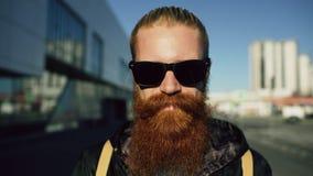Portrait de plan rapproché du jeune homme barbu de hippie dans des lunettes de soleil souriant et posant tandis que rue de déplac photos stock