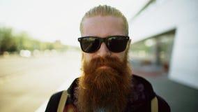 Portrait de plan rapproché du jeune homme barbu de hippie dans des lunettes de soleil souriant et posant tandis que rue de déplac Images libres de droits