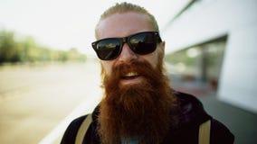 Portrait de plan rapproché du jeune homme barbu de hippie dans des lunettes de soleil souriant et posant tandis que rue de déplac image stock