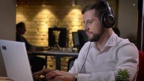 Portrait de plan rapproché du jeune homme caucasien écoutant la musique dans des écouteurs et dactylographiant sur l'ordinateur p banque de vidéos