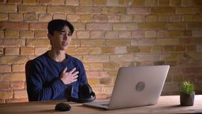 Portrait de plan rapproché du jeune mâle coréen dans des écouteurs passant en revue sur l'ordinateur portable et obtenant bouleve clips vidéos