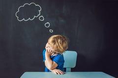 Portrait de plan rapproché du petit garçon mignon pensant profondément au someth Image stock