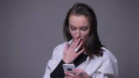 Portrait de plan rapproché du service de mini-messages femelle caucasien attrayant adulte au téléphone et du sourire regardant la clips vidéos
