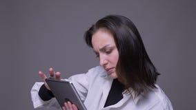 Portrait de plan rapproché du service de mini-messages femelle caucasien attrayant adulte sur le comprimé devant la caméra avec l banque de vidéos