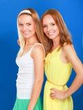 Portrait de plan rapproché du sourire de deux femmes d'isolement sur le fond bleu Photo stock